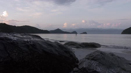 Slider shot of silhouette of male surfer on standup paddleboard an early morning off the beach of Pantai Tengah, Langkawi, Malaysia. Surfing, water sports, SUP, stand-up paddleboarding. Natural look. Stock Footage