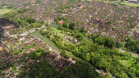 аккуратный : Aerial view in Bali Indonesia : Long. orderly row of structures with tiered. thatched roofs at Pura Taman Ayun. the royal Hindu temple complex in Bali. Indonesia.