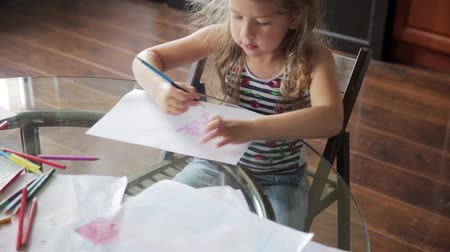 zvýrazňovač : little girl draws with crayons sitting at table Dostupné videozáznamy