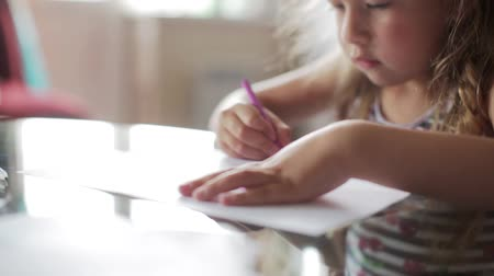 zvýrazňovač : little girl draws with crayons sitting at table. close up Dostupné videozáznamy