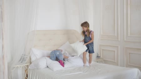 pizsama : two little girls playing and jumping on the bed