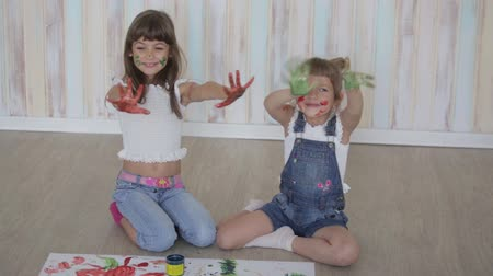 little finger : two little girls draw with finger paints