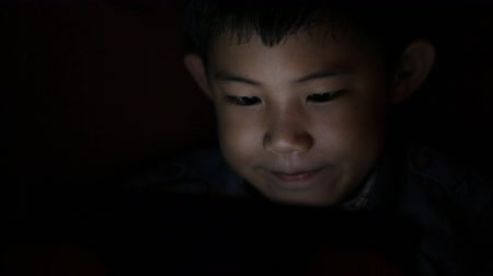 fratellanza : Close up face and hands asian little boy and girl playing computer games lying in his bed in evening. Child using tablet smartphone.