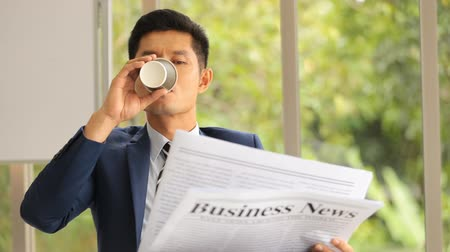 kahve molası : Asian businessman sitting reading newspaper in office smile on face