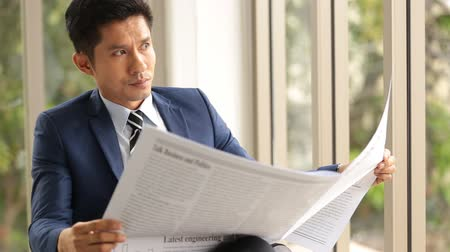 holding newspaper : Asian businessman sitting reading newspaper in office smile on face