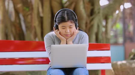 schoolkid : Asian little girl siting and listen to music in the park.