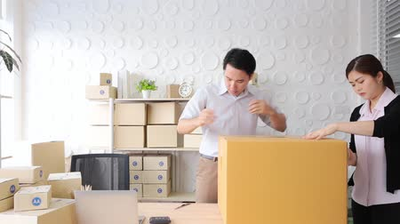 sme : SME concept men and women packing parcel box in office