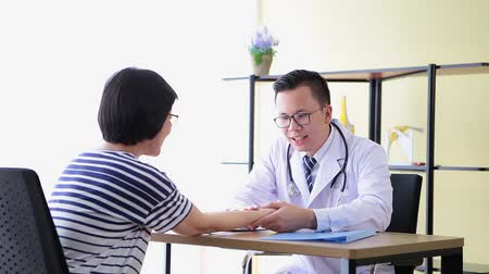 doente : Doctor man checking pulse heart beat of patient in office room Stock Footage
