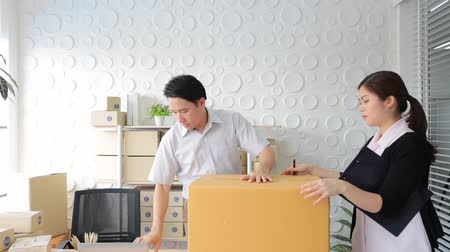 relocate : SME concept men and women packing parcel box in office