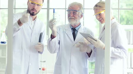 speculate : Science teacher and students team working with chemicals in lab