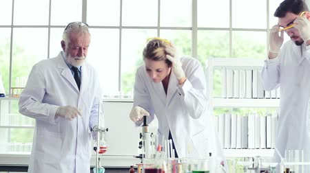 medical student : Science teacher and students team working locking on microscope with chemicals in lab Stock Footage