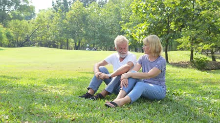 plezant : Elderly couple lovely relaxed sitting on grass in the park