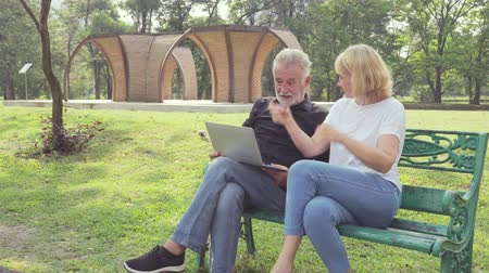 riso : Senior couple using a laptop while sitting on chair in the park