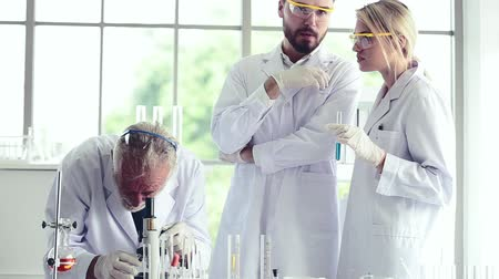 speculate : Science teacher and students team working locking on microscope with chemicals in lab Stock Footage