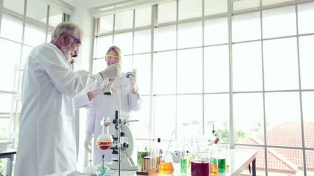 speculate : Chemistry professordoctor team holding tube are using ideas in a lab science