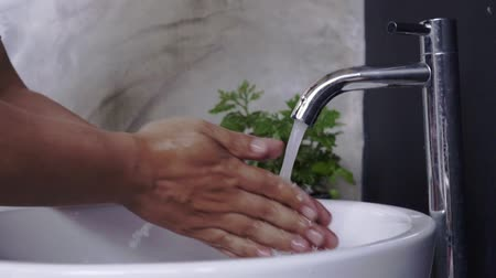 lavatório : Close up of person washing hands in bathroom sink.