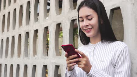 hajló : portrait of a smiling young asian woman standing using smart phone Stock mozgókép