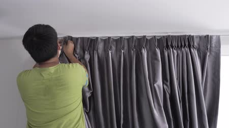 vakok : Man installing curtains gray color on window at home Stock mozgókép