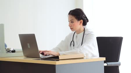apotheker : Asian doctor woman working on laptop medical expertise while sitting at desk in room office