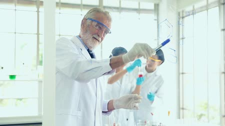 speculate : Science teacher men working with transparent glass board chemicals in lab