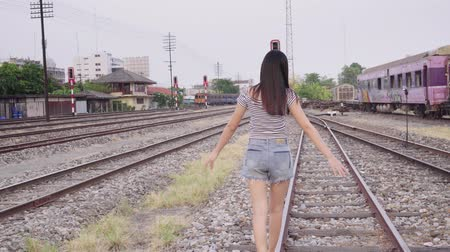 weglopen : Asian hollyday young girl walking on train rail