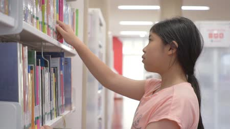 knihkupectví : Asian little girl standing selection book in library