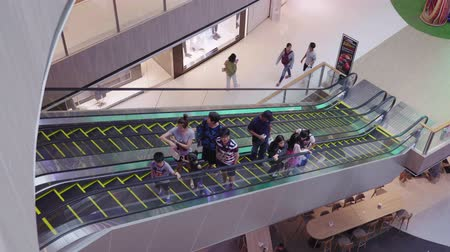 adósság : NAKHONRATCHASIMA, THAILAND - MARCH 2, 2019:Asian people walk up the escalator Happy to shopping In the mall