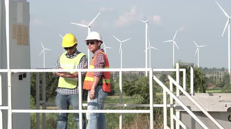 Asian engineer projects the work near the wind turbine