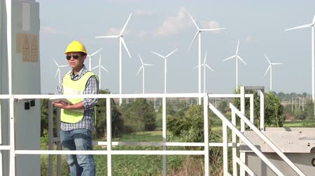 obnovitelný : Asian engineer projects the work near the wind turbine