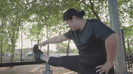 encouraging : Fat Asian women exercise by stretching their legs.