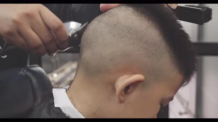 часть тела : Close up hairdresser making hairstyle at asian little boy,Hair cut