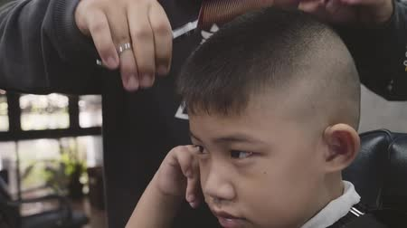 restraining : Close up hairdresser making hairstyle at asian little boy, Hair cut Stock Footage