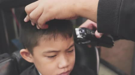 restraining : Close up hairdresser making hairstyle at asian little boy,Hair cut