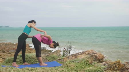 отступление : Asian woman training young girl practicing yoga on mountain background sky and ocean, Healthy active lifestyle concept
