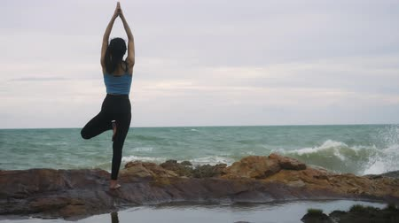 visszavonulás : Asian woman with a slender practicing yoga on mountain background sky and ocean,Healthy active lifestyle concept