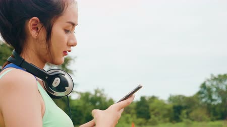 suporte : Lifestyle Asian sport women holding smart phone play music relaxation Stock Footage