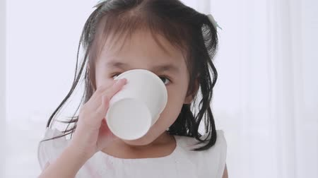 copinho : Closeup face asian little girl holding glass drink water in room
