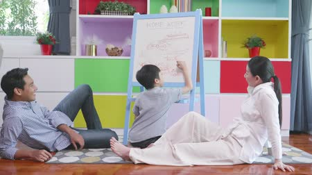 liste : Asian boy writing on board with family in home