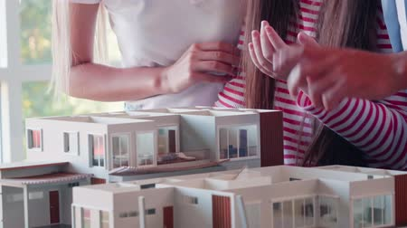 воля : Family looks at the house model that will be built in the future.