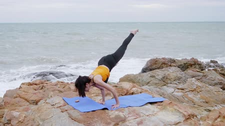 отступление : Asian woman with a slender practicing yoga on mountain background sky and ocean,Healthy active lifestyle concept