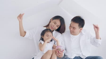 копилку : Mother father holding paper build house, little girl holding piggy bank and putting coins saving building home in the future