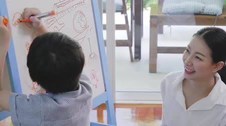 liste : Asian boy writing on board with family in living room