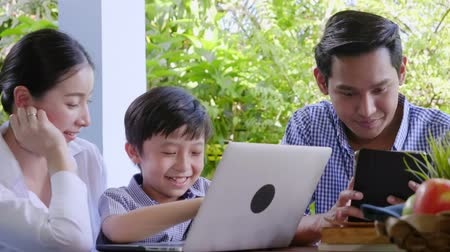 невинный : Asian family laughing and looking in digital laptop while lying home Happy holiday time