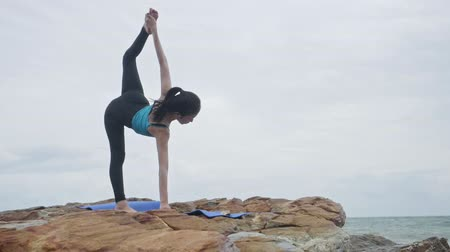 delgado : Asian woman with a slender practicing yoga on mountain background sky and ocean,Healthy active lifestyle concept