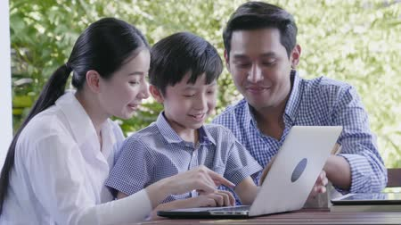 невинный : Asian family laughing and looking in digital laptop while lying on bed in bedroom
