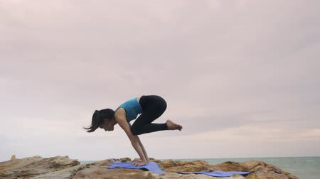 delgado : Asian woman with a slender practicing yoga on mountain background sky and ocean, Healthy active lifestyle concept
