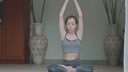 delgado : Asian woman with a slender practicing yoga at home, Healthy active lifestyle concept