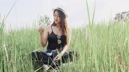 egyetlen virág : Asian woman sitting on meadow in nature Stock mozgókép