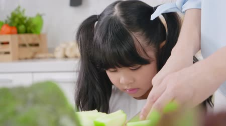 дочь : Asian little girl sitting and watch the phone while eating fruit