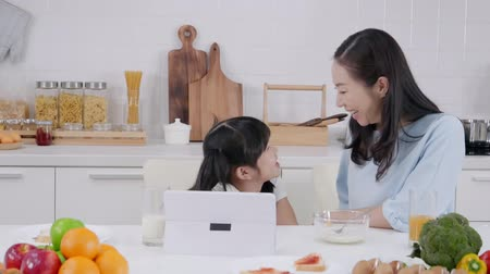 vegetariáni : Family parent and daughter enjoy eating breakfast in kitchen room